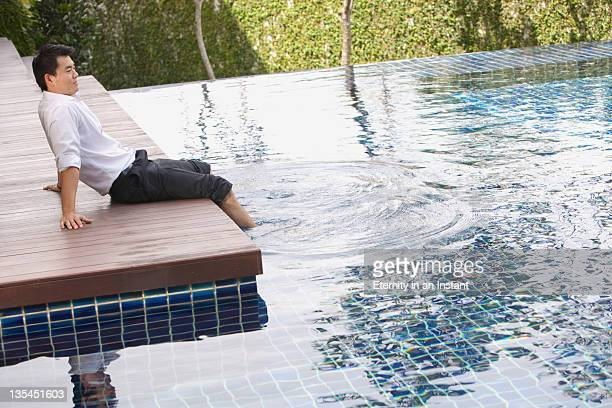 Man relaxing, sitting with feet in pool