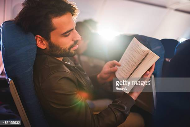 Man relaxing while reading a book in airplane.