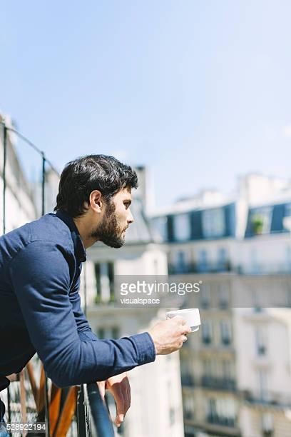 Homme se détendre avec une tasse de café sur un balcon