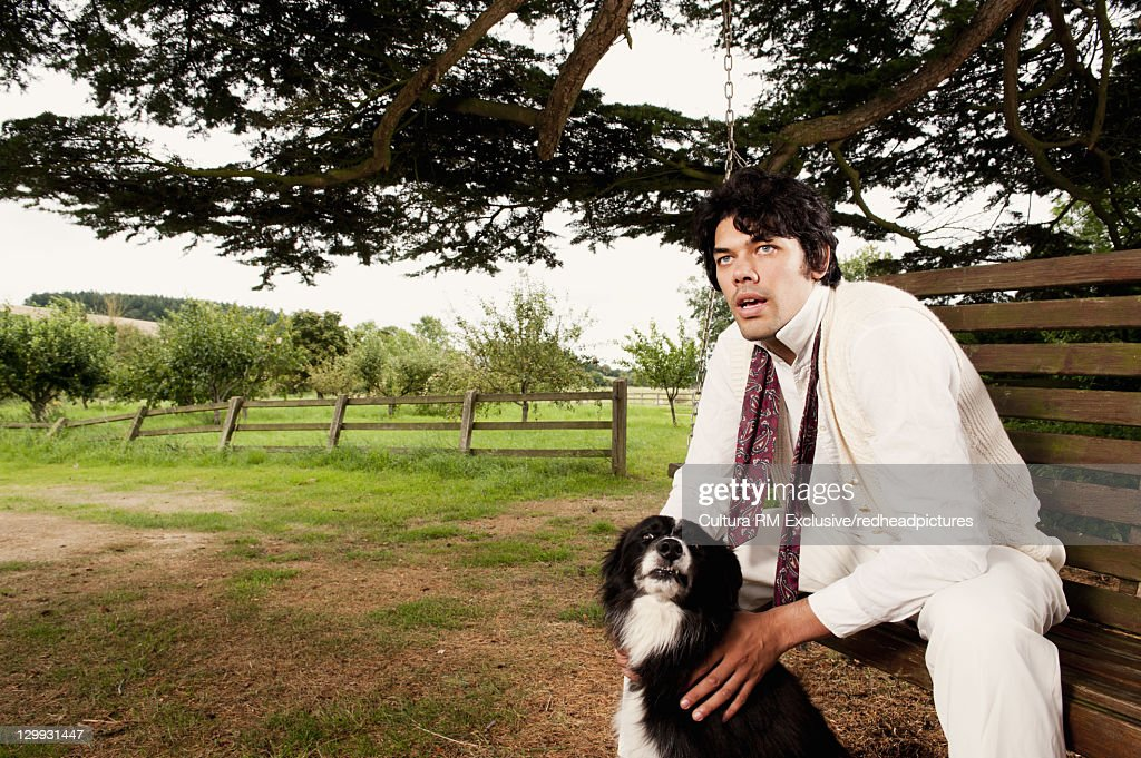 Man relaxing with dog in park : Stock Photo