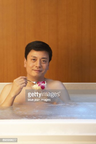 Man relaxing with some fruit in a hot tub : Stock Photo