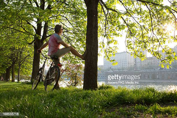 Man releaxes against bike and tree looks to city