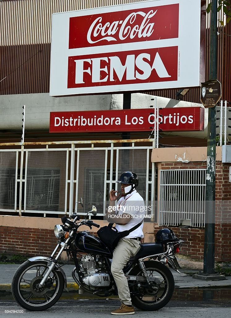 A man remains on his motorcycle outside a Coca-Cola distribution plant in Caracas, on May 25, 2016. Coca Cola suspended much of its distribution in Venezuela due to the lack of sugar. / AFP / RONALDO