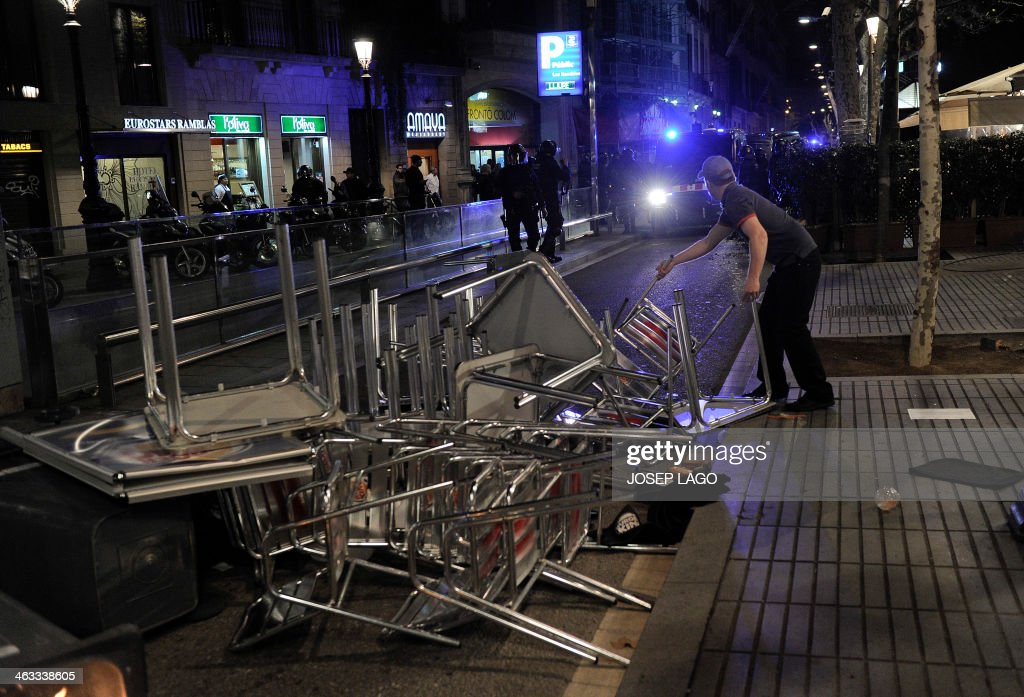 A man removes chairs and tables as demonstrators clash with policemen during a demonstration in Barcelona on January 17, 2014 in support of locals from the city of Burgos protesting against planned construction works to revamp Vitoria street, the city's main thorough-fare. After a week of protest, Burgos' mayor announced today the abandonment of the project. The nightly protests began on January 10 and have spread from Burgos, to Madrid and to the town of Valladolid. AFP PHOTO/ JOSEP LAGO