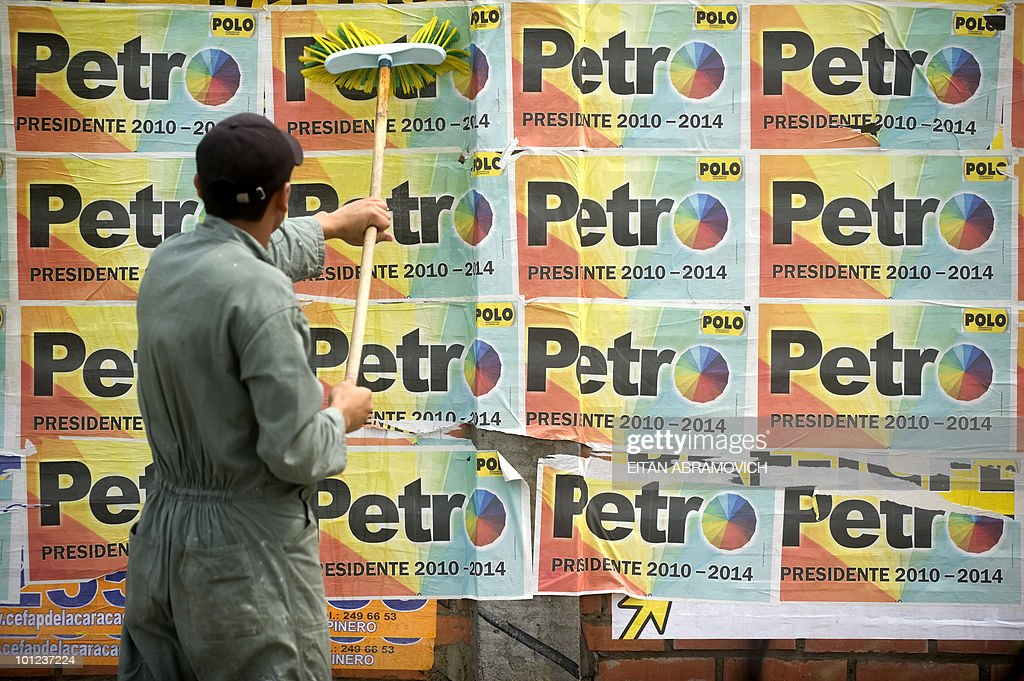 A man removes from a wall propaganda posters of Colombian presidential candidate Gustavo Petro, of the leftist Alternative Democratic Pole Party in Bogota on May 28, 2010. Colombia will hold presidential elections next May 30, and according to polls, a run-off election between Antanas Mockus for the Green Party and Juan Manuel Santos for the ruling National Unity Party, will take place on June 20. AFP PHOTO/Eitan Abramovich
