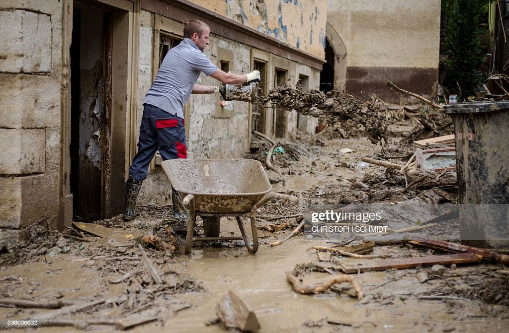 A man removes mud from a house on May 31 2016 in Braunsbach southern Germany hit by the floods after a thunderstorm Cleanup efforts started after...