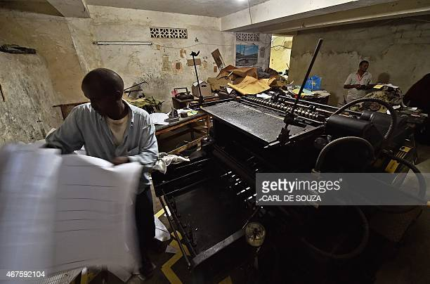 A man removes prints from an old original Heidelberg printing press at the Daha printing press in Mogadishu on March 26 2015 The vintage Germanbuilt...