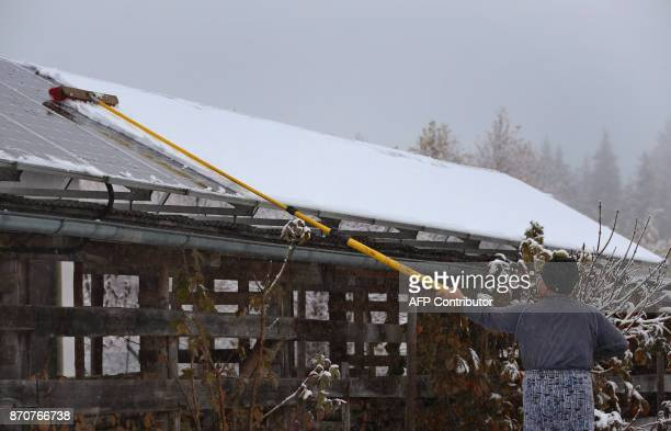 A man removes snow from solar panels covering the roof of a shed near Oy southern Germany after snow fell in the region on November 6 2017 / AFP...