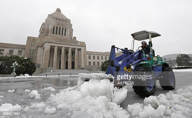 A man removes snow from the forecourt of the Diet building in Tokyo on January 18 2016 Heavy snow blanketed Tokyo metropolitan area and...