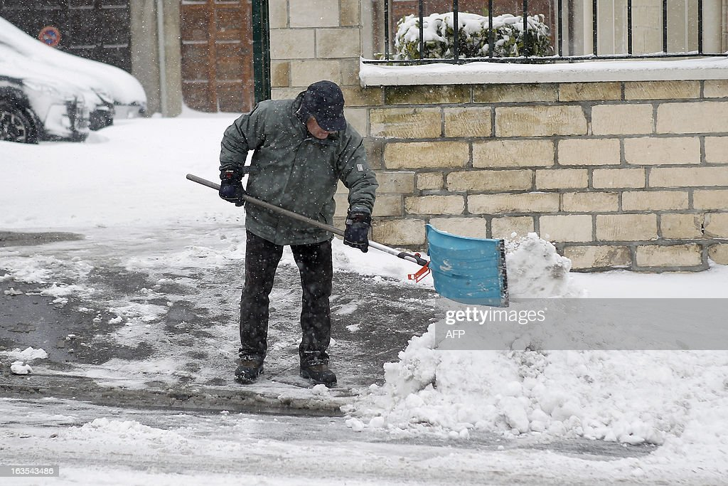 A man removes snow on a snowy sidewalk, on March 12, 2013 in Caen, northwestern France, during a heavy snow storm on France. Overnight Monday nearly 500 cars were blocked near Cherbourg where snowdrifts piled up 60 centimetres (almost two feet) as winds reached 100 kilometres (more than 60 miles) an hour. Twenty-six regions in northwest and northern France were put on orange alert because of heavy snowfalls, which Meteo France said were 'remarkable for the season because of the expected quantity and length of time'.