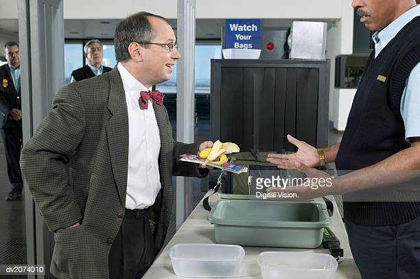 Man Removing a Banana Peel at Airport Customs