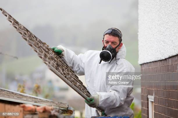 Man removing asbestos from a shed roof of a house in Ambleside, Cumbria