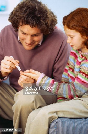 Man removing blood from a young girl's (8-10) finger