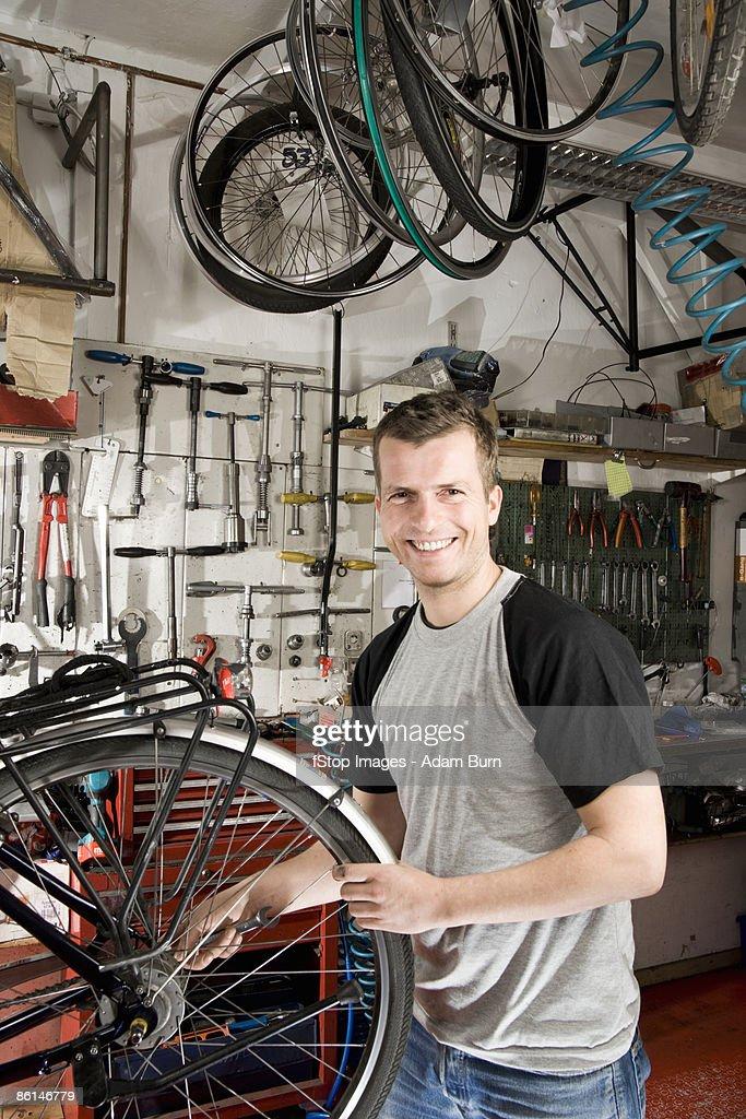 A man repairing a bike in a workshop : Stock Photo