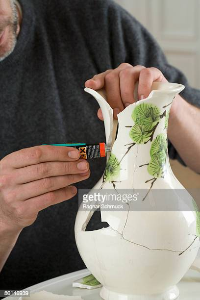 A man repairing a broken vase