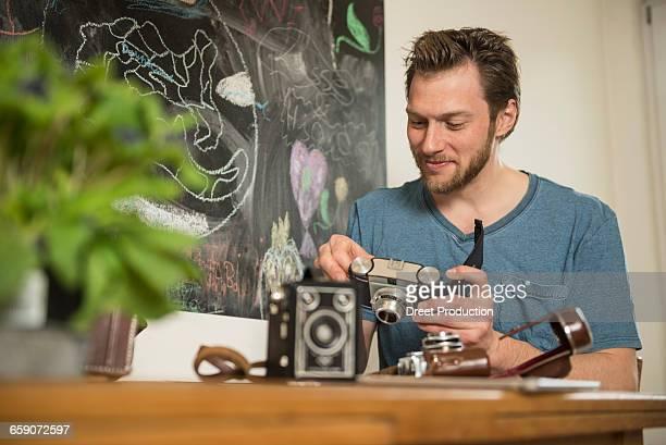 Man repairing antique camera in dining room, Munich, Bavaria, Germany