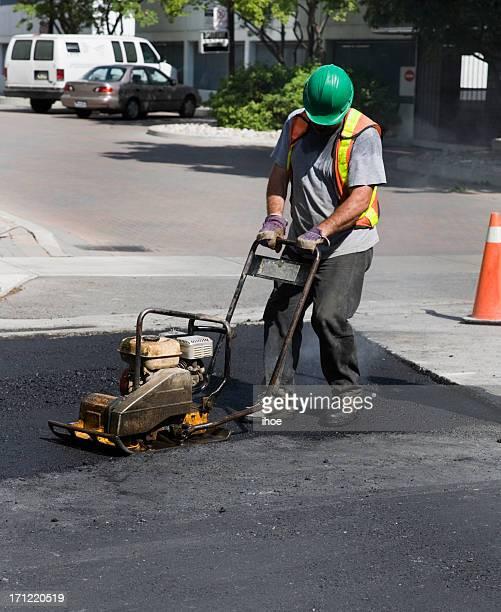 Man repairing asphalt.