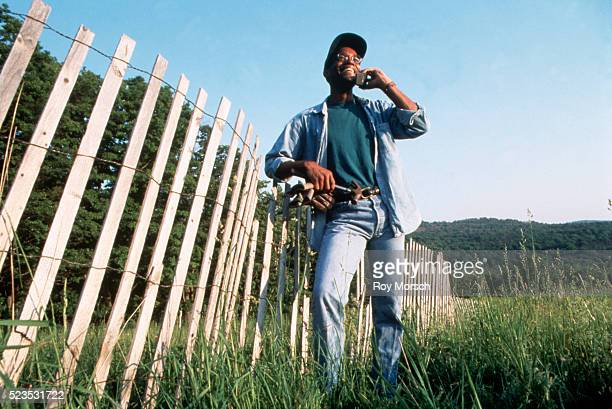 Man repairing fence with cellular phone