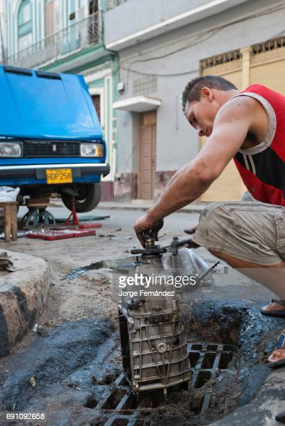 Man repairing his old car engine on the streets of La Habana