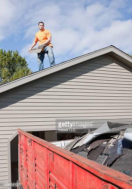 Man repairing roof shingles