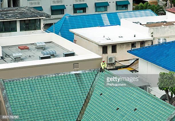 Man repairing rooftop tiles in Honolulu HI