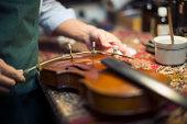Man repairing violin in workshop