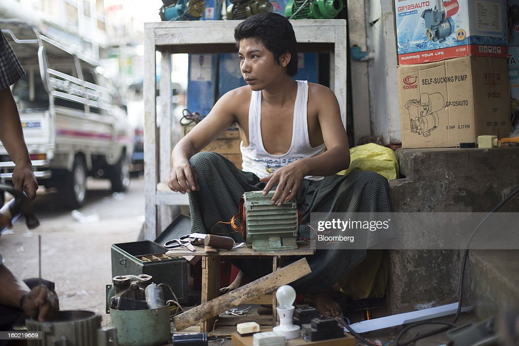A man repairs a water pump in Yangon, Myanmar, on Tuesday, Jan. 22, 2013. Myanmar cleared about $1 billion in overdue debt with the Asian Development Bank and World Bank using a bridge loan from Japan, opening the door for increased lending as the country seeks to overhaul its infrastructure. Photographer: Brent Lewin/Bloomberg via Getty Images