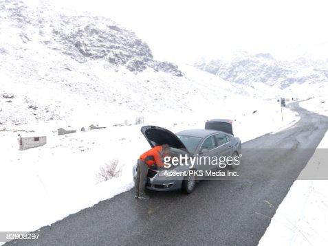Man repairs car at edge of snowy mountain road : Stock Photo