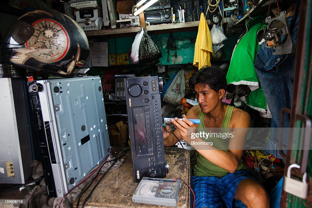 A man repairs electronics at a stall in Manila, the Philippines, on Tuesday, Jan. 22, 2013. Philippine government bonds advanced on speculation the central bank will hold its benchmark interest rate at a record low at a meeting tomorrow, supporting demand for the nation's debt. Photographer: Julian Abram Wainwright/Bloomberg via Getty Images