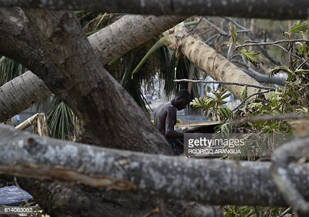 A man repairs his home destroyed by Hurricane Matthew in Port Salut southwest of PortauPrince on October 11 2016 Haiti faces a humanitarian crisis...
