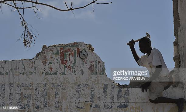 A man repairs his home in Port Salut southwest of PortauPrince on October 12 following the passage of Hurricane Matthew A week after Matthew tore...