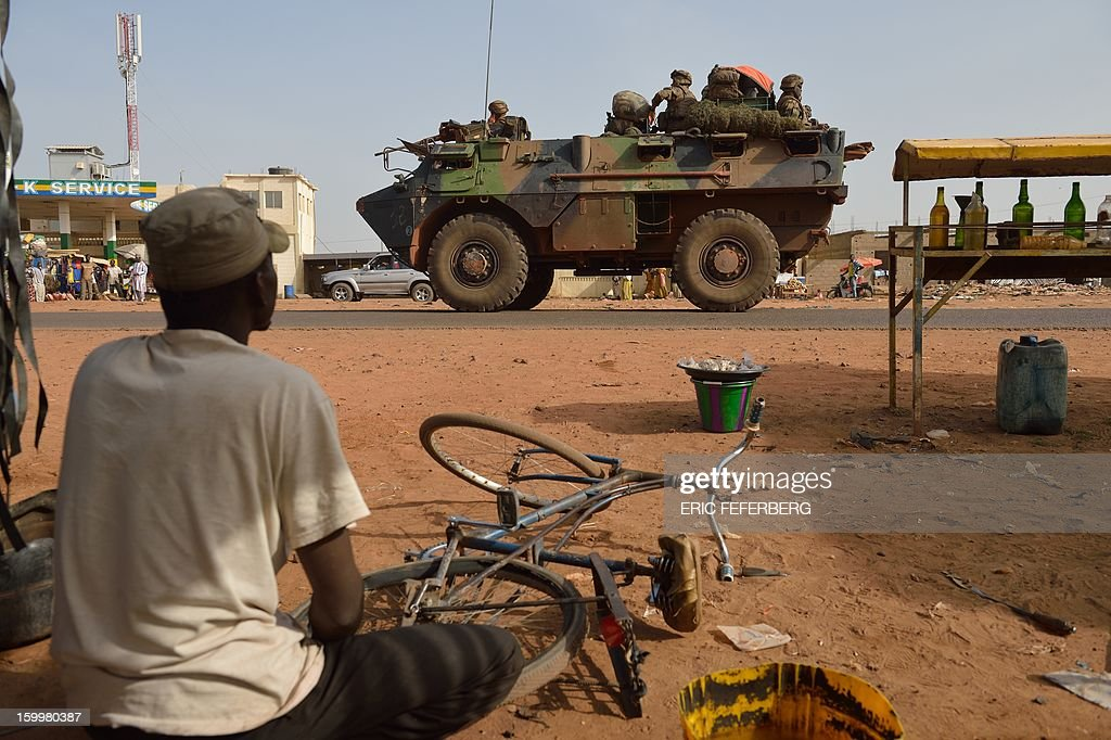 A man reparing the wheel of his bicycle looks at a French armoured vehicle part of a big convoy coming from Bamako and going to Daibali (400km north of Bamako) on January 24, 2013 in Segou. Paris sent in its forces on January 11 to rescue Mali from Al Qaeda-linked groups controlling the north.