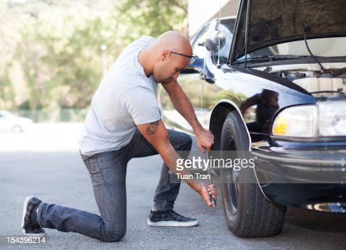 man replacing tire of car