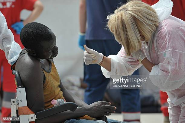A man rescued at sea receives medical assistance as the Italian Navy ship 'Vega' arrives with more than 600 migrants and refugees on May 29 2016 in...