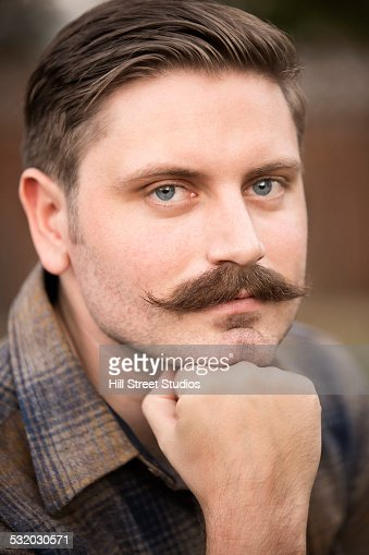 Man resting chin in hand outdoors