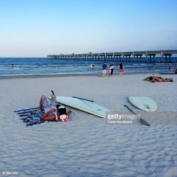 Man resting his head on a soccer ball with surfboards and a paddle or oar close by Jacksonville Beach Florida USA on August 20 2014 just before sunset