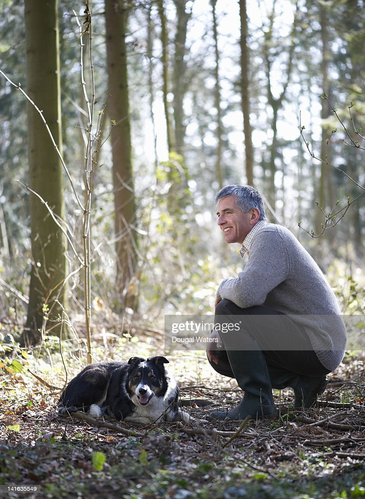 Man resting in woodland with pet dog : Stock Photo