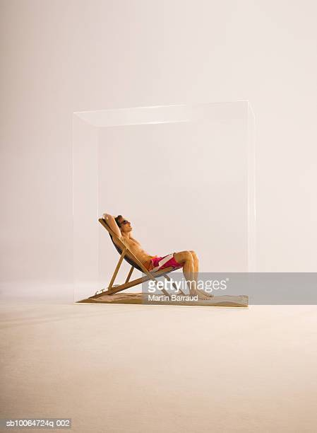 Man resting on deckchair in glass cabinet, side view