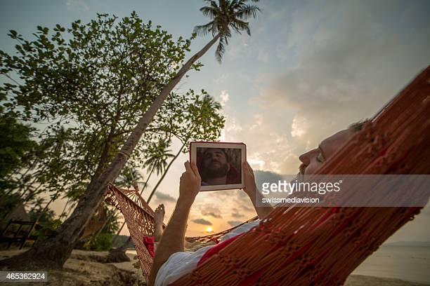 Man resting on hammock on tropical beach-Using digital tablet