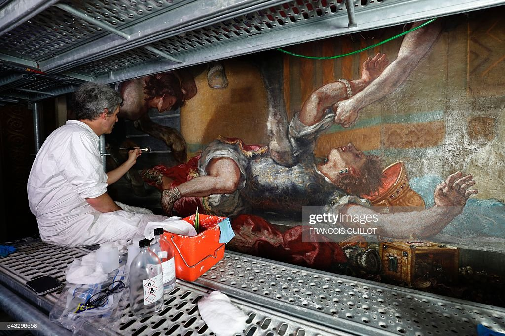 A man restores the Eugene Delacroix paintings made between 1849 and 1861 at the Saints-Anges chapel inside the Saint-Sulpice church in Paris, on June 27, 2016. / AFP / FRANCOIS