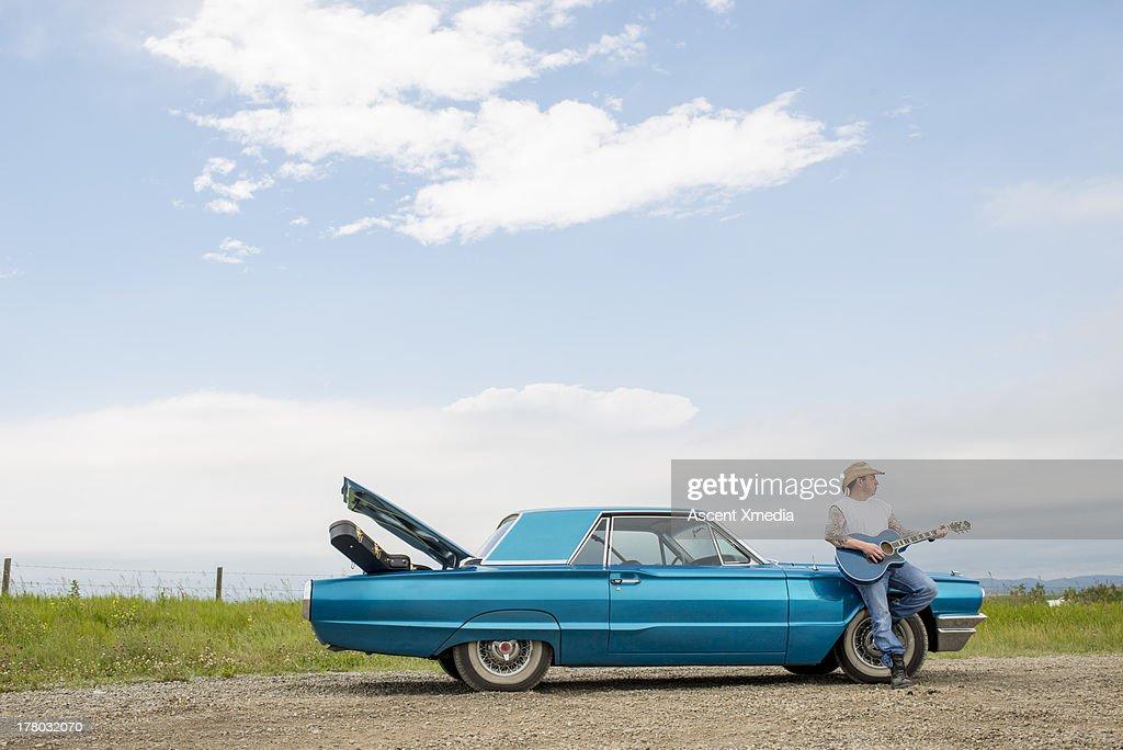 Man rests against older model car, plays guitar : Stock Photo