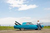 Man rests against older model car, plays guitar