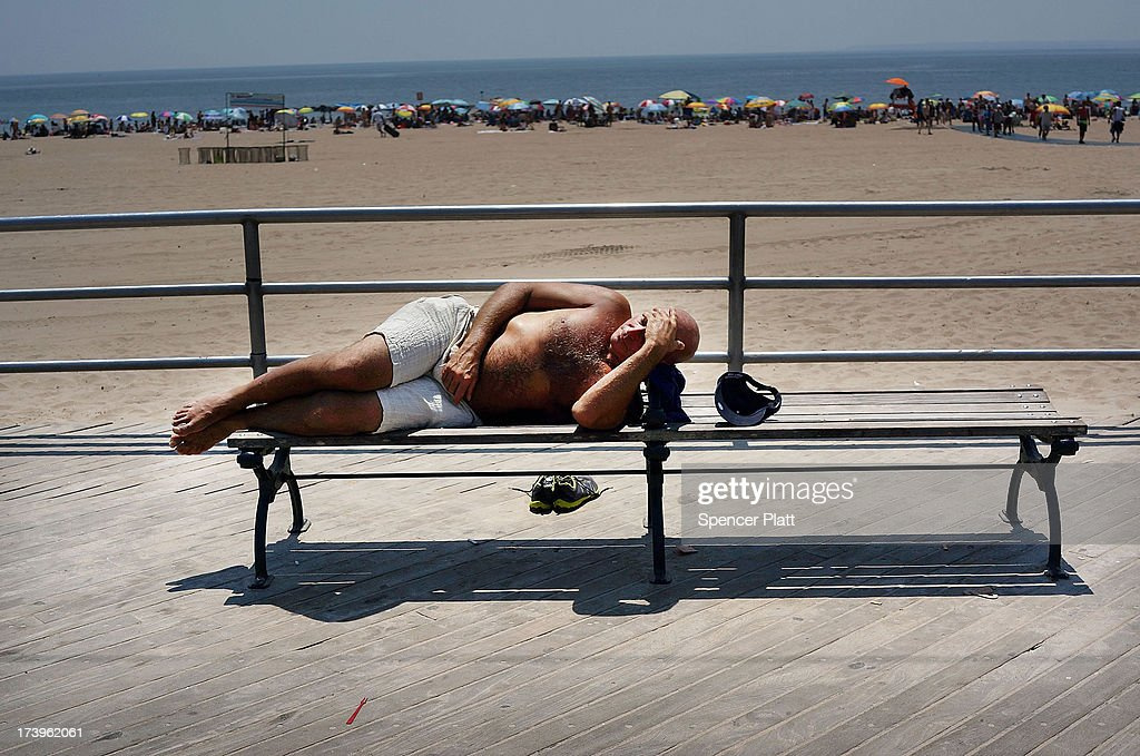 A man rests along the the Coney Island boardwalk on one of the hottest weeks in recent New York City history on July 18, 2013 in New York City. With daily temperatures in the high 90's and with the heat index making it feel in the triple digits, many New Yorkers are doing what they can to stay cool. A break from the heatwave is not expected until Saturday evening at the earliest.