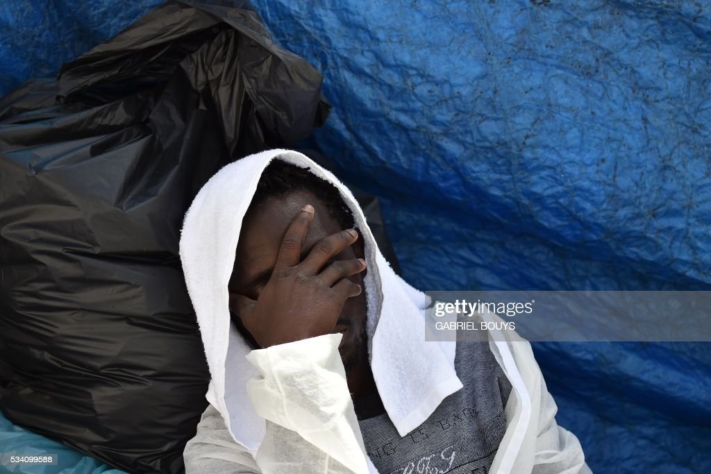 A man rests as he waits for a meal aboard the rescue ship 'Aquarius', on May 25, 2016 a day after a rescue operation of migrants and refugees off the Libyan coast. The Aquarius is a former North Atlantic fisheries protection ship now used by humanitarians SOS Mediterranee and Medecins Sans Frontieres (Doctors without Borders) which patrols to rescue migrants and refugees trying to reach Europe crossing the Mediterranean sea aboard rubber boats or old fishing boat. / AFP / GABRIEL