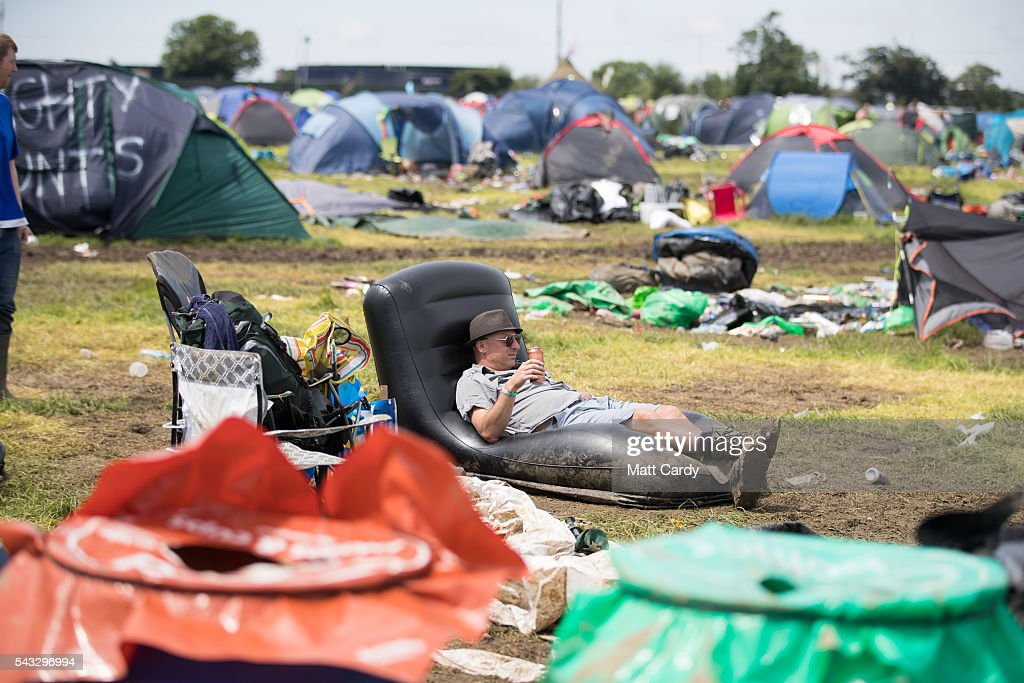 A man rests beside his tent as festival goers leave the Glastonbury Festival 2016 at Worthy Farm, Pilton on June 26, 2016 near Glastonbury, England. The Festival, which Michael Eavis started in 1970 when several hundred hippies paid just £1, now attracts more than 175,000 people.