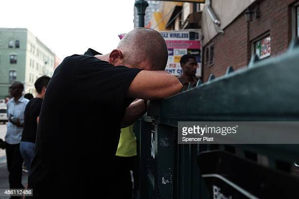 A man rests his head on the railing of a subway entrance in an area which has witnessed an explosion in the use of K2 or 'Spice' a synthetic...