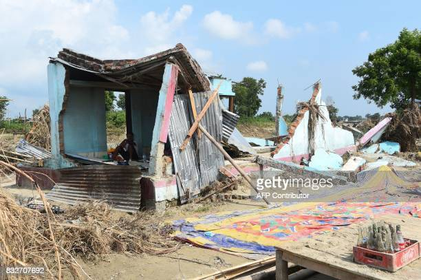 A man rests in his damaged house hit by flood in Itahari Sunsari district some 250 kms from Nepal's capital Kathmandu on August 16 2017 At least 221...