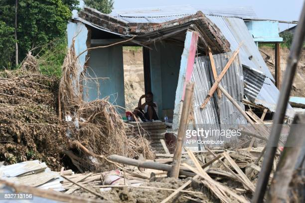 A man rests in his house damaged by flood in Itahari Sunsari district some 250 kms from Nepal's capital Kathmandu on August 16 2017 At least 221...