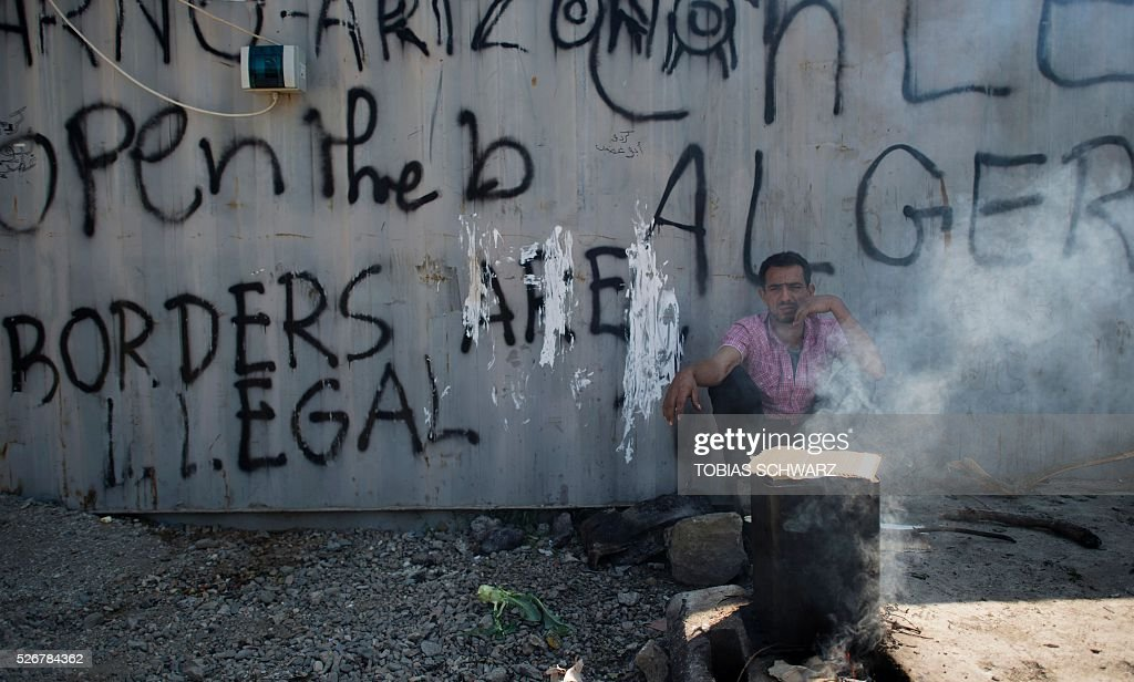 A man rests in the shade against a wall with the lettering 'Borders are illegal' at a makeshift camp for migrants and refugees near the village of Idomeni not far from the Greek-Macedonian border on May 1, 2016. Some 54,000 people, many of them fleeing the war in Syria, have been stranded on Greek territory since the closure of the migrant route through the Balkans in February. / AFP / TOBIAS