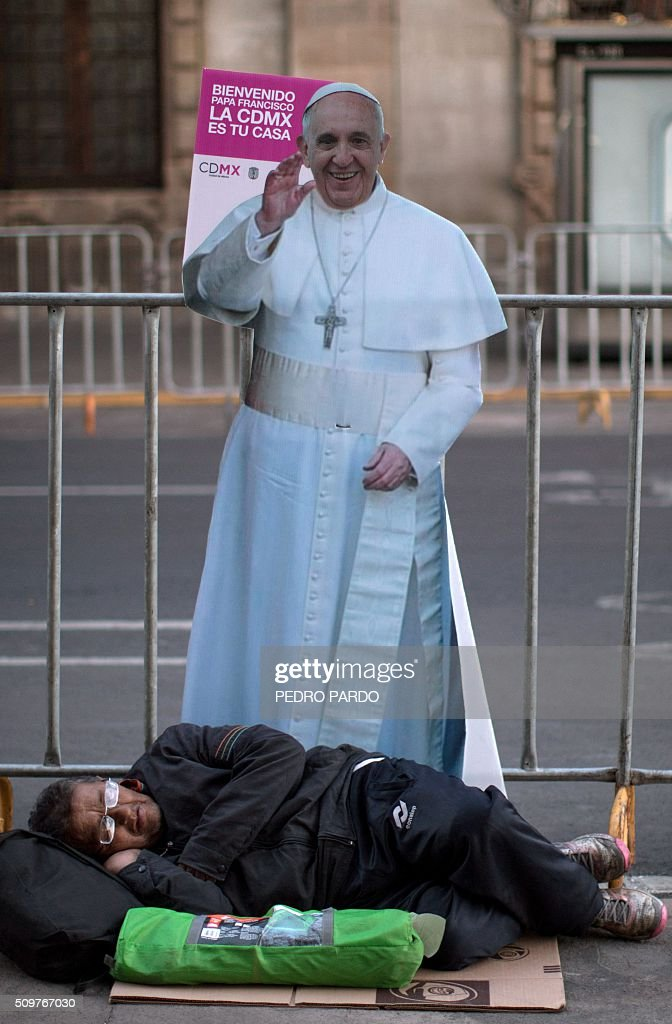 A man rests next to an image of Pope Francis, in Mexico City on February 12, 2016 hours before the arrival of the pontiff to the country. Pope Francis left Rome on Friday bound for Cuba, where he is to hold a historic meeting Russian Patriarch Kirill before continuing on to Mexico for a five-day visit. AFP PHOTO / Pedro PARDO / AFP / Pedro PARDO